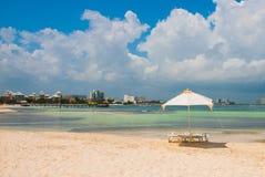 太阳懒人和伞游人的海滩的在坎昆,墨西哥 库存图片