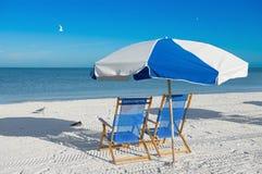 太阳懒人和沙滩伞 免版税库存图片