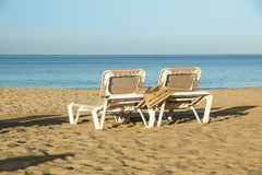 太阳懒人和闭合的伞在海滨胜地,暑假的镇静和轻松的大气在日落 库存图片