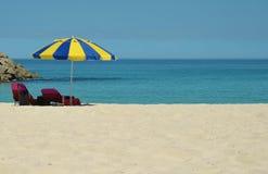 太阳懒人在海滩的一把伞下 库存照片