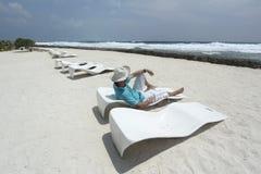 太阳懒人的人在海滩 库存图片