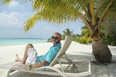 太阳懒人的人在Maldivian海滩的棕榈树下 免版税库存图片