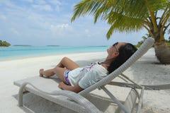 太阳懒人的女孩在Maldivian海滩的一棵棕榈树下 免版税库存图片