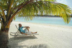 太阳懒人的秃头人在Maldivian b的一棵棕榈树下 免版税库存图片