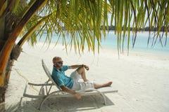 太阳懒人的秃头人在Maldivian b的一棵棕榈树下 库存照片