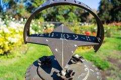 太阳时钟在玫瑰园 库存图片