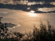太阳是在一朵灰色云彩后 免版税库存图片