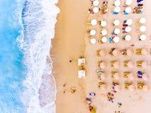 太阳椅子和伞鸟` s在希腊注视在沙子海滩的看法 图库摄影