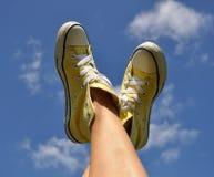 太阳烧了在明亮的黄色运动鞋的妇女的脚反对深刻的蓝天背景 免版税库存照片