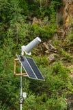 太阳电池板供给通信站天线动力有自然峭壁和植被背景 库存照片