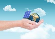 太阳电池板和地球在手边在天空 图库摄影