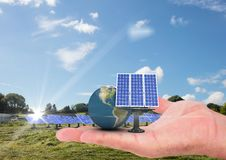 太阳电池板和地球在手边在湖附近 图库摄影