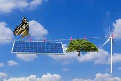 太阳电池板和垂悬在与蝴蝶的晾衣绳的风轮机和树 免版税库存图片