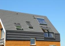 太阳电池板和太阳水加热器在现代房子屋顶有天窗的和屋顶窗室外为节能 免版税库存图片