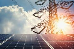 太阳电池板和高压塔与阳光 清洁能源p 免版税库存照片