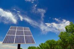 太阳电池板在与树和云彩的一个晴天 库存图片