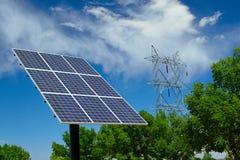 太阳电池板在与高压电压输电线的一个晴天 图库摄影