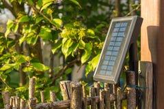 太阳电池板在庭院里,提供三带领光以能量 免版税库存图片