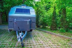 太阳电池板是固定的在旅游拖车 越野拖车在厚实的绿色叶子背景的停车场站立  免版税库存图片