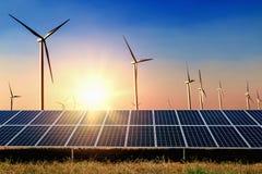 太阳电池板有涡轮和日落蓝天背景 概念 免版税库存图片