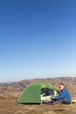 太阳电池板附加帐篷 坐在手机旁边的人从太阳充电 免版税库存照片