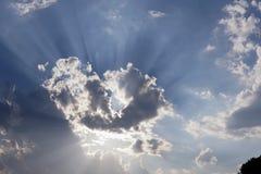 太阳的光芒在天空背景,心形的白色云彩的 库存照片