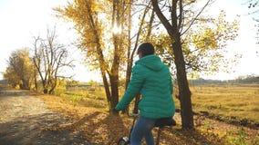 太阳的光芒照亮的桃红色夹克骑马自行车的少女在秋天公园 慢的行动 股票视频