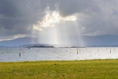 太阳的光芒从在海洋的云彩的后面 免版税库存照片