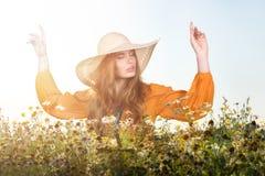 太阳的喜悦 站立在领域的帽子的少妇 库存照片