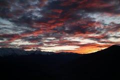 太阳的最后光芒从山的后面照亮了在虚幻的美好的颜色的云彩 免版税库存照片