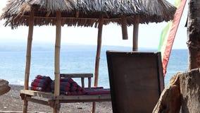 从太阳的木风雨棚眺望台在浪漫海滩在巴厘岛 靠岸与黑火山沙子在Amed,在巴厘岛东部 股票录像