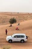 太阳的游人等和中止汽车下来在迪拜的沙丘 免版税库存图片