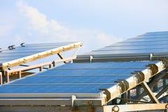 太阳能电池产生的电能在太阳光,蓝色光致电压的太阳电池板特写镜头,安全世界的绿色能量之前 图库摄影