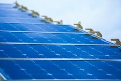 太阳能电池产生的电能在太阳光,蓝色光致电压的太阳电池板特写镜头,安全世界的绿色能量之前 库存照片