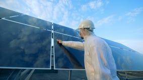 太阳能电池板阵列的反射性表面的清洗的过程由一名男性工作者举行了 绿色能量概念 股票录像