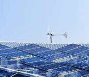 太阳能电池盘区和风轮机在工厂屋顶有城市scr的 免版税库存图片