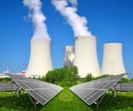 太阳能盘区在一个核电站前 库存照片