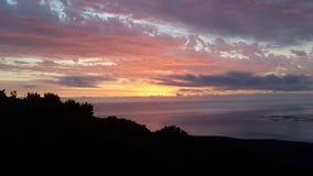 太阳落下和光束在海洋 免版税库存照片