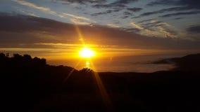 太阳落下和光束在海洋 库存图片