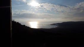 太阳落下和光束在海洋 图库摄影