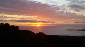 太阳落下和光束在海洋 免版税图库摄影