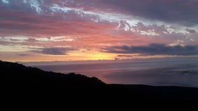 太阳落下和光束在海洋 免版税库存图片