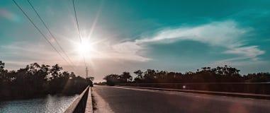 太阳设置了在接近大西洋的出海口的一座桥梁在拉各斯尼日利亚非洲 免版税库存图片