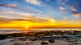 太阳设置在大西洋的天际的橙色天空下阵营的在开普敦附近咆哮 免版税图库摄影