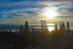 太阳设置在有些云彩后的一个冷的冬日 库存图片
