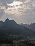 太阳通过在村庄的山的云彩发光 库存图片