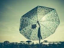 太阳通过沙滩伞 免版税库存照片