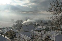 太阳通过重的云彩发光在镇Slovenska用雪盖的Lupca 免版税库存图片