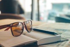 太阳镜、日志、笔和报纸在桌上 免版税图库摄影