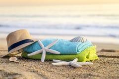 太阳镜、毛巾、帽子、太阳块、壳和海星在含沙 库存照片